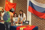 <p>A student look at the items on display at the Russian table exhibit, overseen by Alisa Matlakhova, sitting, and Anna Klimenteva, on her left, ASU students from Russia.</p>