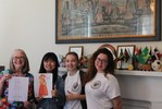 <p>Peggi Wolfe, Global Programs Specialist, Jin Cheng, Chinese FLTA, Anna Klimenteva and Alisa Matlakhova show winning drawing from interactive lesson and Jin is holding the original picture she described. </p>