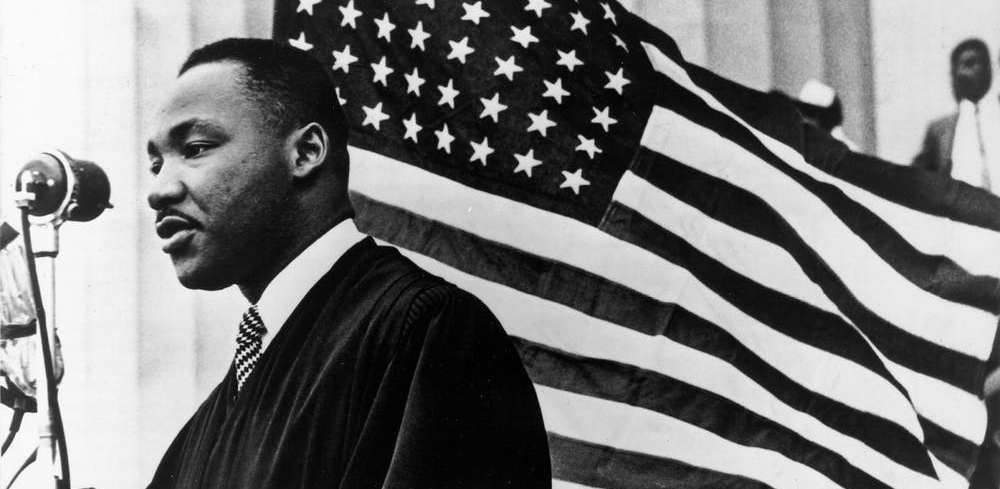 A picture of Martin Luther King Jr. speaking into a microphone, standing in front of a American flag.